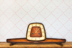 Vintage table clock in front of retro wallpaper Stock Image