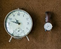 Vintage table clock and man`s wristwatch on a brown background. Artwork. Top view Royalty Free Stock Image