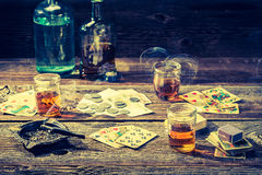 Vintage table for illegal poker with vodka, cigarettes and cards Royalty Free Stock Photos