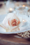 Vintage table setting with beige rose. Festive table decoration, vintage table setting with beige rose, candles and antique cutlery Stock Photography