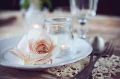 Vintage table setting with beige rose. Festive table decoration, vintage table setting with beige rose, candles and antique cutlery Stock Photo