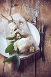 Vintage table setting with floral decorations. Napkins, white roses, leaves and berries on a wooden board background Stock Images