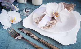 Vintage table setting with orchid decorations on a blue background. Tinted. Royalty Free Stock Photo