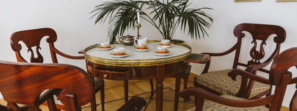 Vintage table for tea-drinking and wooden chairs Stock Photography