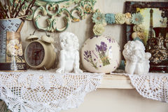 Vintage table with two angels, clocks and knitted cloth Royalty Free Stock Image