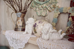 Vintage table with two angels, clocks and knitted cloth Stock Photo