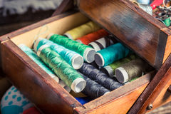 Vintage tailor's wooden box with threads, needles and buttons Stock Photo