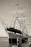 A vintage tall ship is docked in harbor Stock Photography