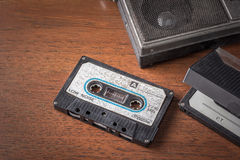 Vintage tape cassette with old radio on wooden table background Royalty Free Stock Photo