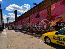 Vintage Taxi Cab in Street Art Alley in Baltimore. A vintage Checker Cab parked in an alley in Baltimore, Maryland MD. The alley is covered in hot pink street stock photography
