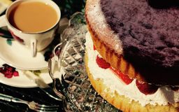 Tea and Victoria Sponge Cake. Vintage tea cup and saucer with Victoria sponge cake on a glass cake stand Stock Image