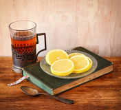Vintage tea glass-holder with fresh lemons and old book over wooden table. retro filtered image Stock Photos