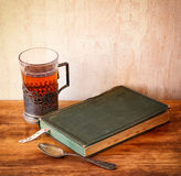 Vintage tea glass-holder with fresh lemons and old book over wooden table. retro filtered image. Royalty Free Stock Photo
