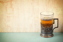 Vintage tea glass-holder over wooden table. retro filtered image Stock Photo