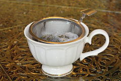 Vintage tea strainer and tea ready in cup Royalty Free Stock Image
