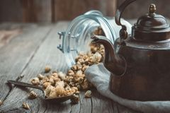 Vintage teapot and glass jar of dry healthy chamomile buds on table. Copy space for text. stock photo