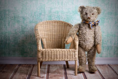 Vintage Teddy bear. Unsightly vintage Teddy bear with wicker chair Royalty Free Stock Photos