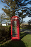 Vintage telephone box. Vintage British red telephone box set under a shady tree on green grass Royalty Free Stock Images