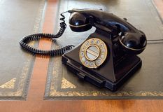 Vintage telephone on desk. An old, vintage telephone standing on the desk, decorative surface Stock Images