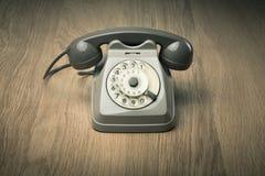 Vintage telephone on hardwood surface. Vintage gray telephone on hardwood surface desk or floor Royalty Free Stock Images