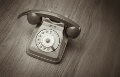 Vintage telephone on hardwood surface Stock Photos