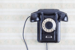 Vintage telephone on old retro wall paper. Vintage telephone close up on old wall Royalty Free Stock Images