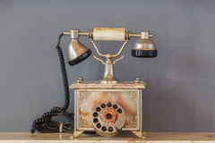 Vintage telephone on old table sepia photo Royalty Free Stock Photo