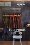Vintage Telephone Operator's Desk. Vintage telphone operator's desk - telephone office chair with old phone and switchboard in background Royalty Free Stock Image