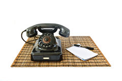 Vintage telephone on rattan mat with black pen and notepad with copyspace Stock Images