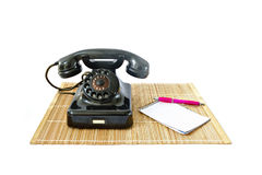 Vintage telephone on rattan mat with pink pen and notepad with copyspace Royalty Free Stock Photography