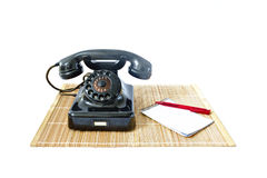 Vintage telephone on rattan mat with red pen and notepad with copyspace Royalty Free Stock Photography