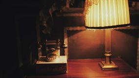Vintage telephone and retro desk lamp on table stock footage
