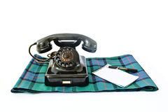 Vintage telephone on tartan plaid with black pen and notepad with copyspace. Isolated on white background Royalty Free Stock Photo