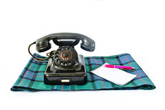 Vintage telephone on tartan plaid with pink pen and notepad with copyspace. Isolated on white background Royalty Free Stock Photography