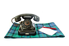 Vintage telephone on tartan plaid with red pen and notepad with copyspace Stock Photography
