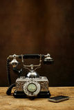 Vintage telephone on wooden table and a mobile phone. Stock Photo
