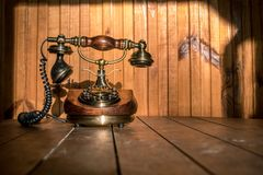Vintage telephone on wooden table with wooden background at sun royalty free stock image