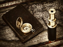Vintage telescope and compass at antique map. Travelling theme: the vintage telescope, compass and an old Bible at antique map (15 century Stock Photos