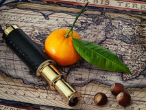 Vintage telescope and mandarine at antique map. Travelling theme: vintage telescope and mandarine at antique map Stock Photography