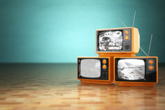 Vintage television concept. Stack of retro tv set on green backg Royalty Free Stock Image
