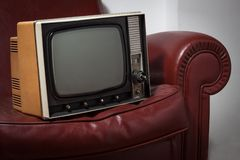 Vintage television on a couch. Vintage television on a red leather couch Royalty Free Stock Images