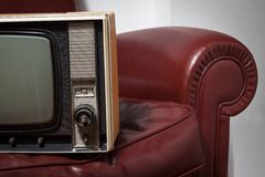 Vintage television on a couch. Vintage television on a red leather couch Royalty Free Stock Photo