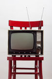 Vintage television on a red chair. Against white background Royalty Free Stock Image