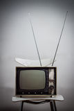 Vintage television on a white chair. Against white background Stock Photos