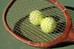 Vintage Tennis Racquet and Balls. Vintage Tennis Racquet and two new tennis balls plus shadow on center court royalty free stock image