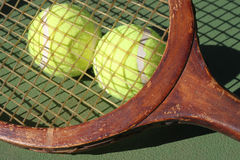 Vintage Tennis Racquet and Balls Closeup. Vintage Tennis Racquet closeup and two new tennis balls plus shadow on center court royalty free stock image