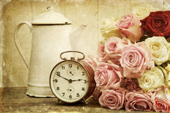 Vintage textured still life with roses and alarm clock. Vintage textured still life picture with an old enamel coffee can, an old alarm clock and a romantic rose royalty free stock photos