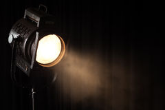 Vintage theater spot light on black curtain
