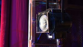 Vintage theater spotlight on black curtain with dust floating in front.  stock video footage