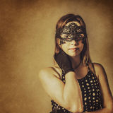 Vintage theatre show girl. Luxury portrait of a pretty young broadway theatre performer wearing old-fashioned masquerade mask at gala show. Vintage theatre Royalty Free Stock Photography